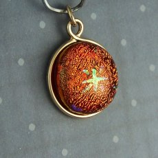 Small red-orange dichroic glass star pendant with 14k gold setting
