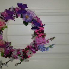 Wreath decorated with artificial flowers and butterflies