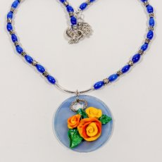 Hand sculpted multi-colored clay roses on polymer disk necklace